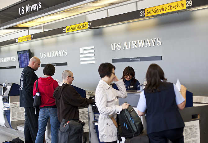 US Airways passengers check in for their flights at Charlotte Douglas International Airport in Charlotte, North Carolina.