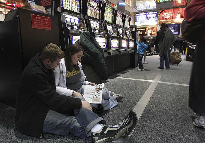 Ryan Caille and Megan Wile of Houston do crossword puzzles at McCarran International Airport in Las Vegas, Nevada.