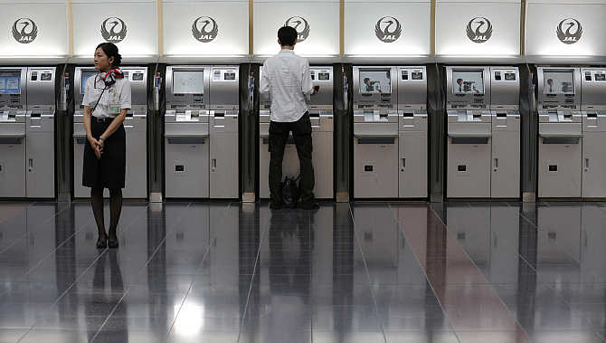 An employee of Japan Airlines stands in front of ticket machines at Tokyo International Airport, Japan.