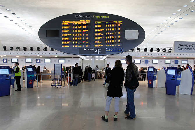 Passengers look at a flight departure information board in a terminal at the Charles-de-Gaulle airport in Roissy, near Paris.