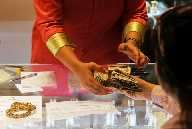An employee receives payment from a customer inside a gold jewellery showroom in Mumbai.