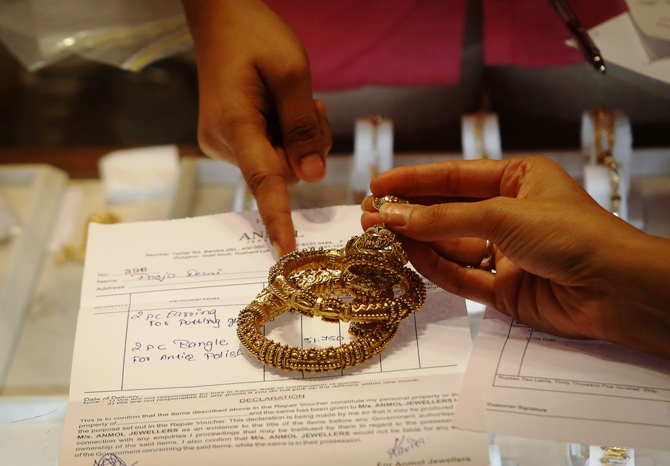An employee explains the bill to a customer as gold bangles are placed on top of it inside a jewellery showroom in Mumbai.