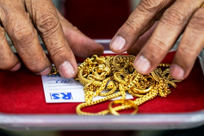 A pawn shop worker sorts through gold jewellery at Easy Money Pawn shop.