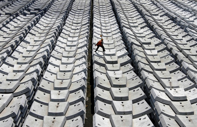 A worker walks over giant pieces of concrete that will be used to make tunnels for the metro railway, at a casting yard in Chennai.