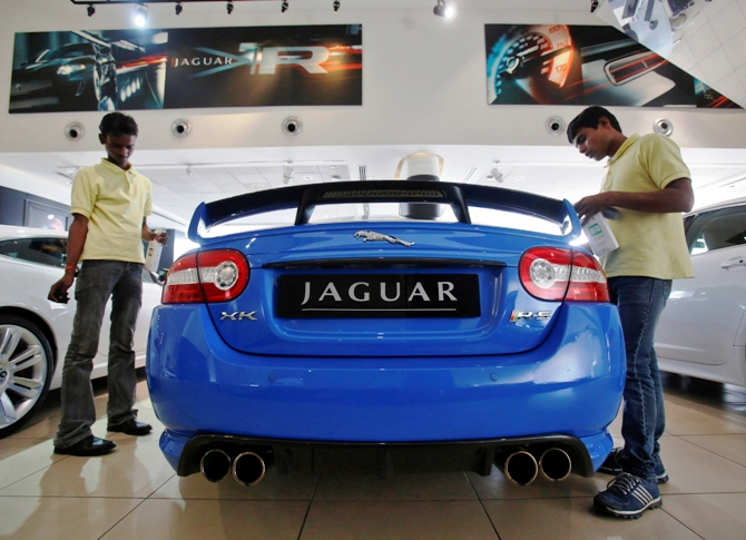 Showroom attendants polish a Jaguar vehicle at a Jaguar Land Rover showroom in Mumbai.