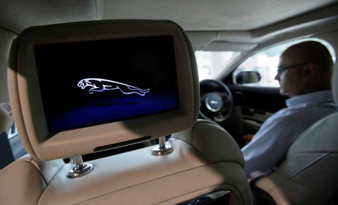A man sits inside a Jaguar vehicle as he demonstrates its features at a Jaguar Land Rover showroom in Mumbai.