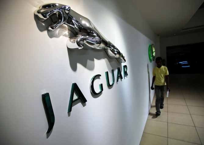A showroom attendant walks past company logos at a Jaguar Land Rover showroom in Mumbai.