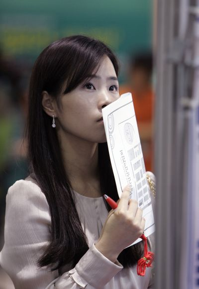 A woman looks at job adverts at a job fair.