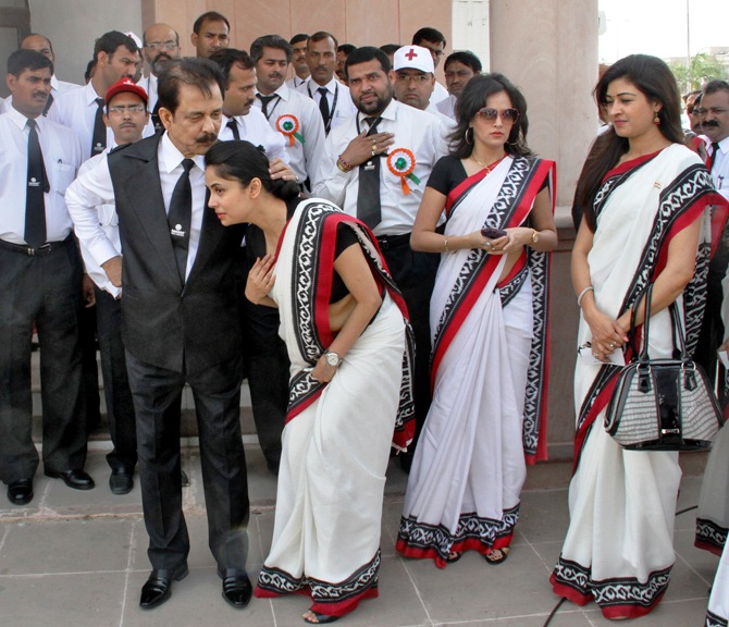 Sahara Group Chairman Subrata Roy (front, L) speaks with an employee before they sing India's national anthem in Lucknow.