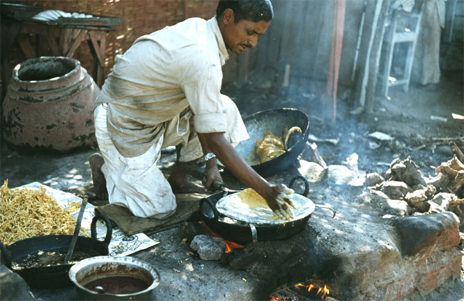 A man makes traditional morning bread.