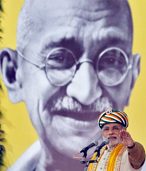 Gujarat's chief minister Narendra Modi addresses a gathering in front of a portrait of Mahatma Gandhi during his day-long fast at Godhra, Gujarat on January 20, 2012.