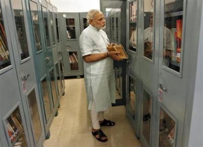 Modi looks at books in a library inside his residence.