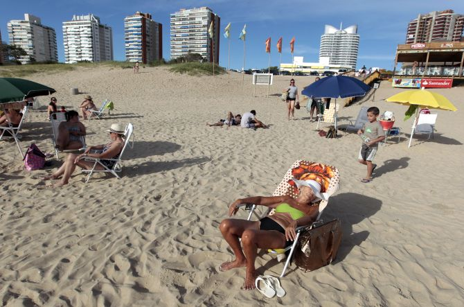 People sunbathe at the beach of the luxurious seaside resort of Punta del Este.