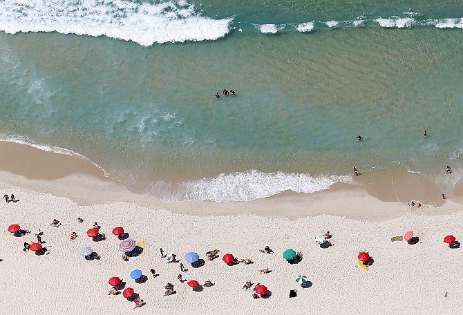 People enjoy the Barra da Tijuca beach in Rio de Janeiro.