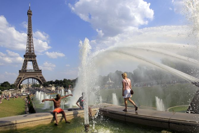 People cool off in a fountain of the Trocadero Square in front of the Eiffel Tower on a warm summer afternoon in Paris.
