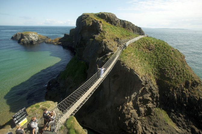 Torchbearer Denis Broderick holds the Olympic Flame on the Carrick-a-Rede rope bridge.