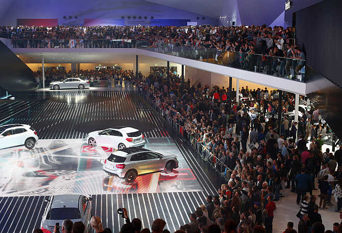 Visitors watch a car presentation at the stand of German manufacturer Mercedes Benz at the Frankfurt Motor Show, Germany.