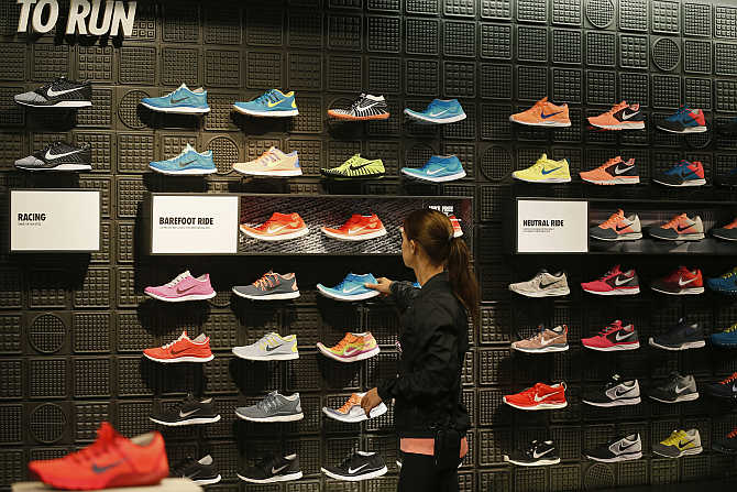 A woman picks up a shoe in the Nike store in Santa Monica, California.