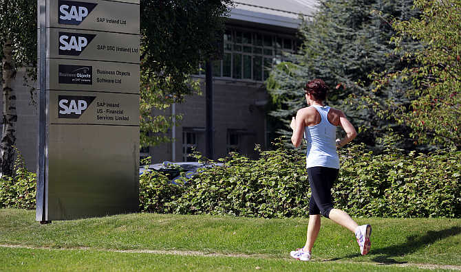 A woman jogs past the SAP offices in the CityWest complex, Dublin, Ireland.