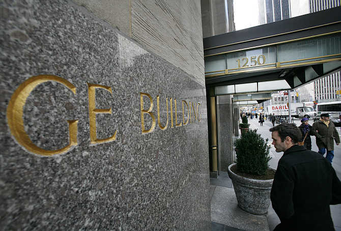A man enters the General Electric building at 1250 Avenue of the Americas, also known as 30 Rockefeller Plaza, in New York City.