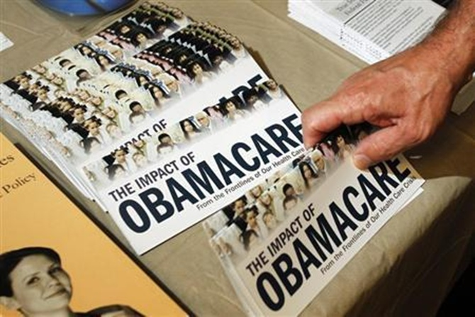 A Tea Party member reaches for a pamphlet titled ''The Impact of Obamacare'' in Littleton, New Hampshire.