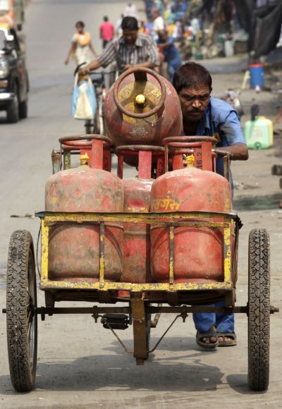 An employee of a cooking gas agency pushes a rickshaw loaded with gas cylinders in Mumba.