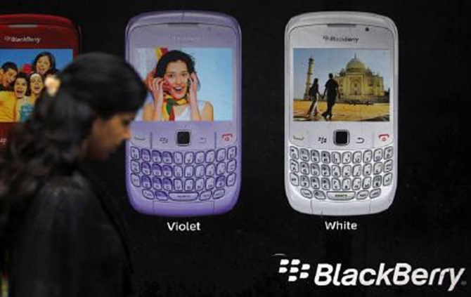 A woman walks past a Blackberry advertisement billboard.