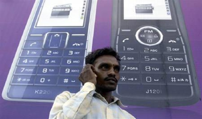 A man speaks on a mobile phone in front of a billboard.