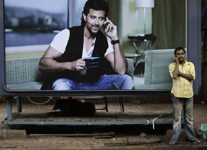 A man makes a phone call on his mobile phone in front of an advertisement  in Mumbai.