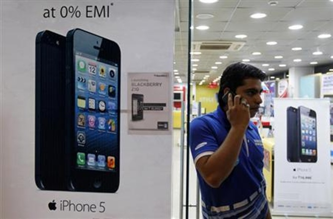 A man speaks on his mobile phone while standing next to posters advertising an Apple iPhone 5 and Blackberry Z10 in Ahmedabad.