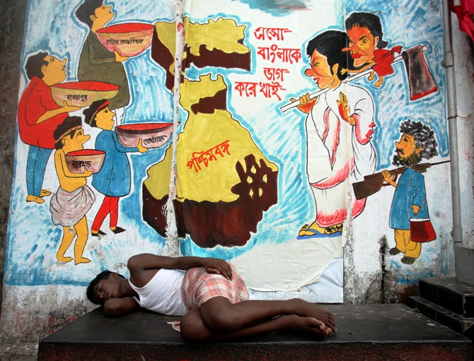 This file photograph shows a man sleeping in front of graffiti in Kolkata on April 30, 2009.