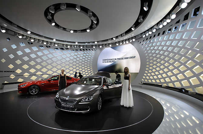Models pose in front of BMW 6 Series Gran Coupe cars in Geneva.