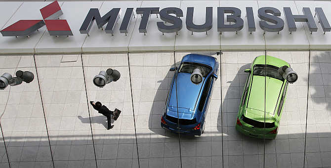 Mitsubishi Motors's vehicles and a passer-by are reflected on an external wall at the company headquarters in Tokyo.