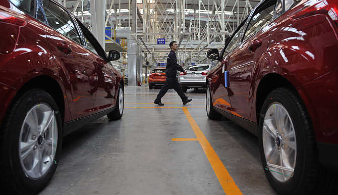 An employee walks past newly assembled cars at a Ford manufacturing plant in Chongqing municipality in China.