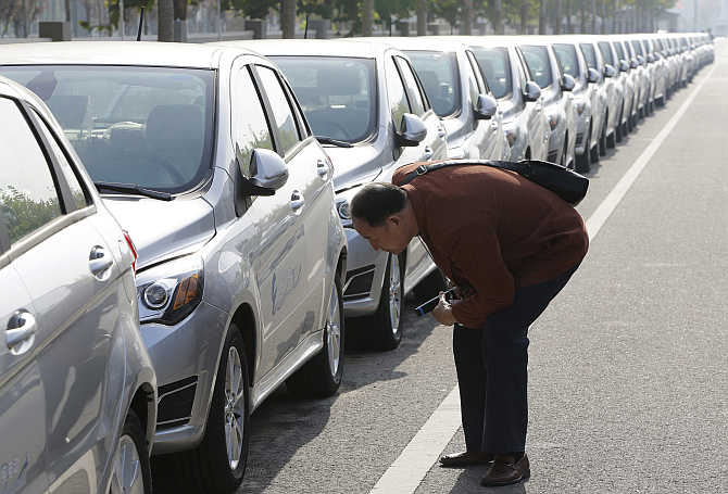 A visitor looks at a Beiqi E150EV car in Beijing.