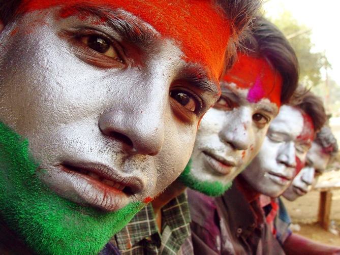 Indians sit with their faces painted with the colours of the Indian national flag as they celebrate Holi in Bhopal.