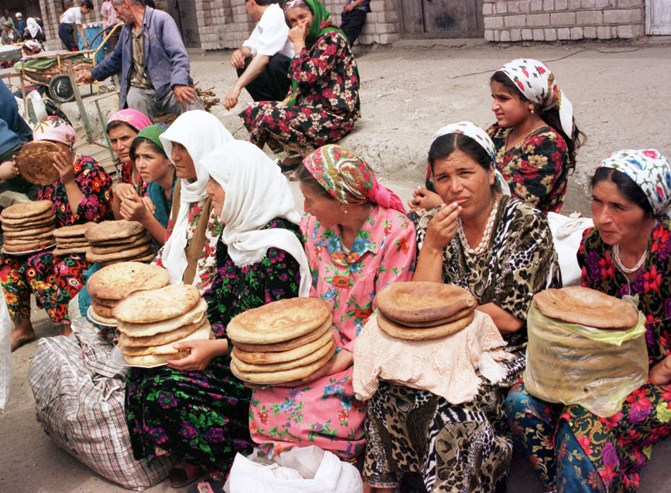 Tajik women sell bread in a street market.