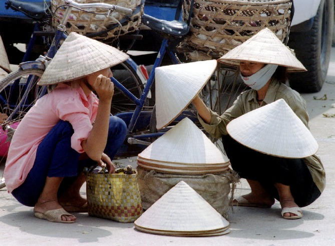 A Vietnamese woman buys conical hats called 'non' from a sidewalk vendor in Hanoi.