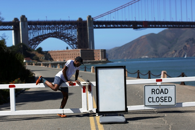 A runner climbs over a road gate leading to Fort Point National Historic Site, which has been closed due to the federal government shutdown, in San Francisco, California.