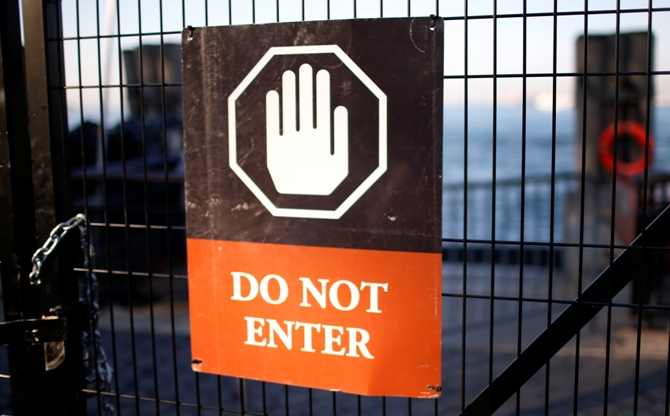 A sign hangs on a fence at the ticket entrance to the Statue of Liberty, a US National Park, due to the US Government shutdown.
