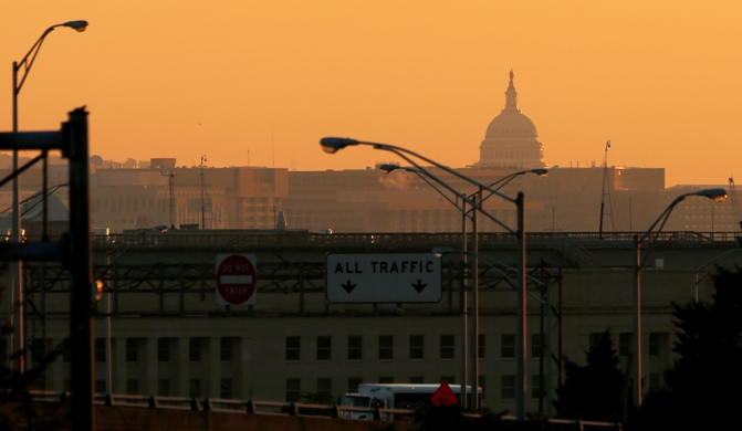 The dome of the US Capitol rises over the Pentagon and other federal buildings in Washington during sunrise.