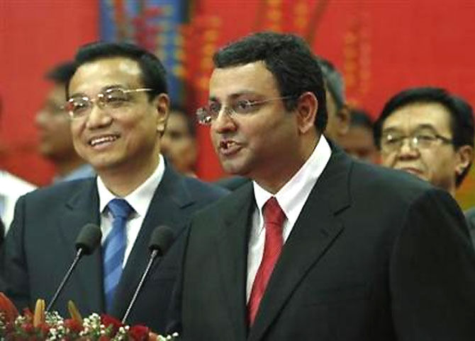 Tata Group chairman Cyrus Mistry speaks as China's Premier Li Keqiang (L) looks on at an office of software services company TCS in Mumbai on May 21, 2013.