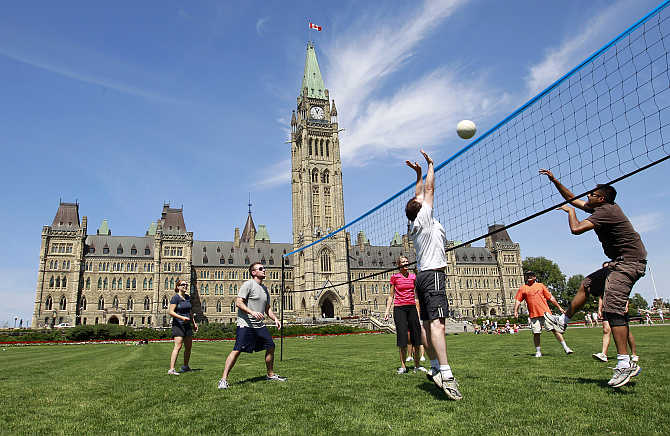 People play volleyball on the front lawn of Parliament Hill in Ottawa, Canada.