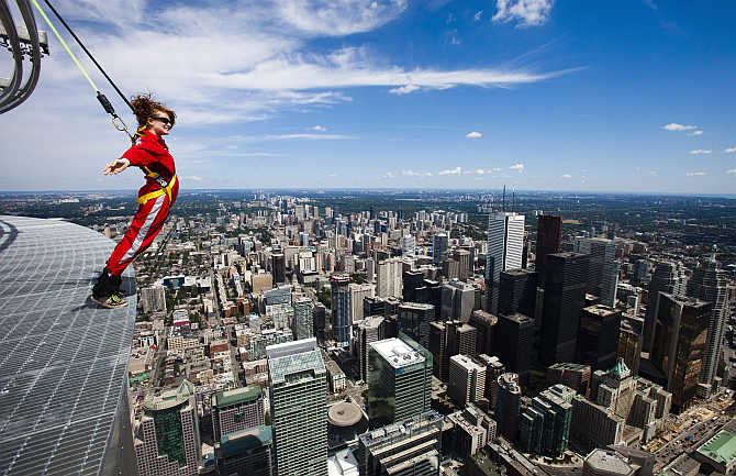 A reporter leans over the edge of the catwalk during the media preview for the 'EdgeWalk' on the CN Tower in Toronto, Canada.