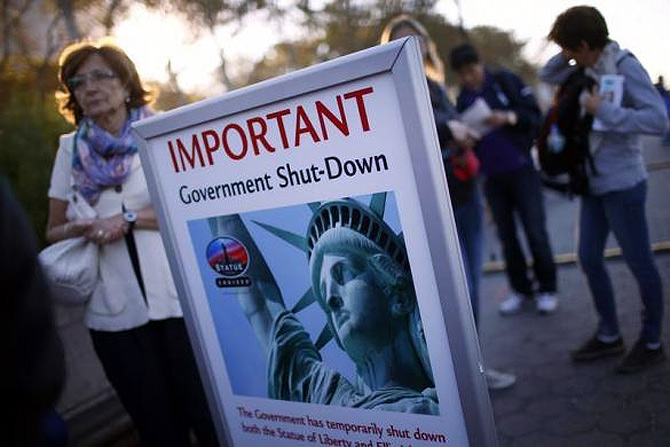 Tourists stand next to a sign announcing the closure of the Statue of Liberty, a US National Park, due to the US Government shutdown near the ferry dock to the Statue of Liberty in Battery Park in New York.