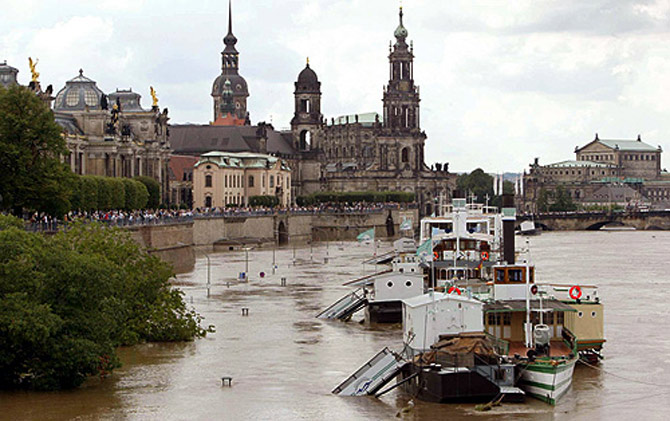 Boats are seen floating above the piers on a flooded street in front of the historic skyline of Dresden, along the banks of the river Elbe.