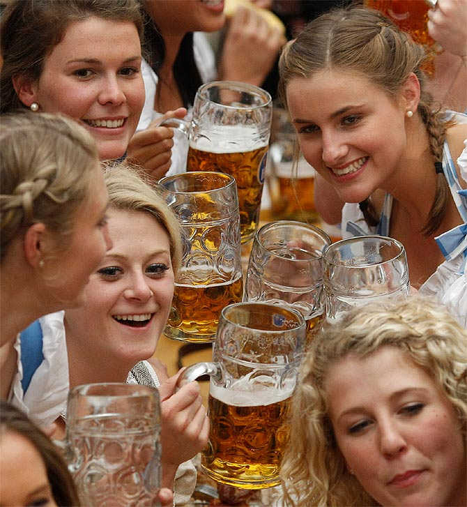 People wearing traditional Bavarian clothes toast with beer at the Oktoberfest in Munich, Germany.