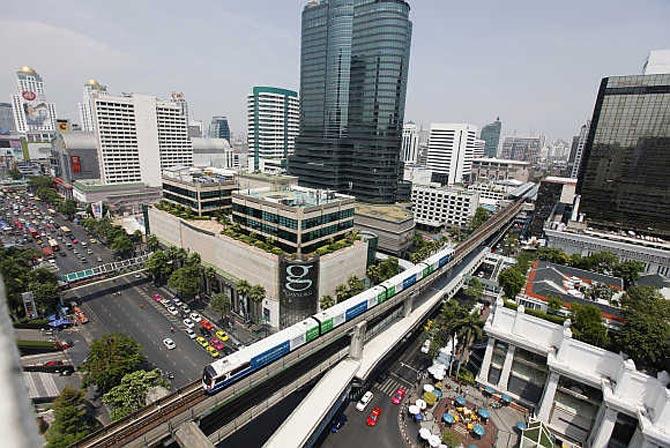 A skytrain passes over vehicles in Bangkok, Thailand.
