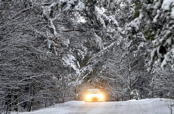 A car is seen on a road after heavy snowfall in Torun, northern Poland.
