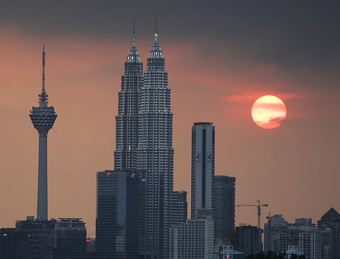 The sun sets near the Petronas Twin Towers (C) and Kuala Lumpur Tower (L).